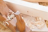 pic of wood craft  - Close up view of a wooden handheld wood plane used to smooth and level the surface of a plank of wood surrounded with fresh wood shavings in a DIY woodworking carpentry or joinery concept