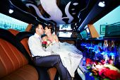 stock photo of fiance  - Bride and groom in wedding limousine with yellow and black colors - JPG