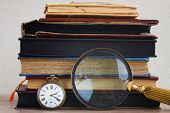 stock photo of vintage antique book  - antique clock with loupe  on pile of  vintage books background - JPG