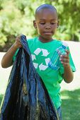 picture of pick up  - Little boy in recycling tshirt picking up trash on a sunny day - JPG