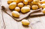 pic of root-crops  - Farm fresh baby potatoes displayed on a hessian sack on a rustic wooden table at farmers market a healthy nutritious root vegetable popular in vegetarian and vegan cuisine