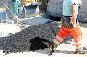 stock photo of tar  - Men hard working on asphalting road - JPG