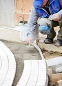 picture of banquette  - Mason worker making sidewalk pavement with stone blocks - JPG