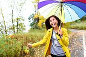 picture of girl walking away  - Autumn woman happy in rain running with umbrella - JPG