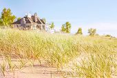 stock photo of dune grass  - Dune grasses with beach house - JPG