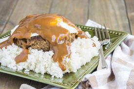 stock photo of loco  - Loco Moco a traditional Hawaiian dish of teriyaka flavored ground beef patty and a fried egg on a bed of rice smothered in gravy - JPG