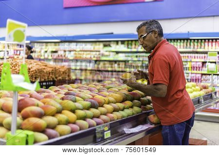 Consumer buying some fresh mangos at the supermarket