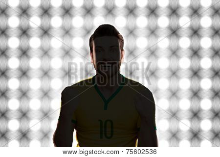 Soccer player celebrates on a light painel background.