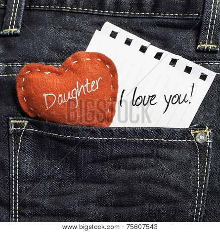 Daughter I love you! written on a peace of paper and a heart on a jeans backgroundD
