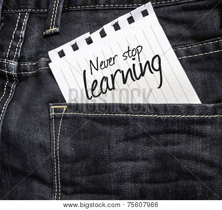 Never Stop Learning written on a peace of paper on a jeans background