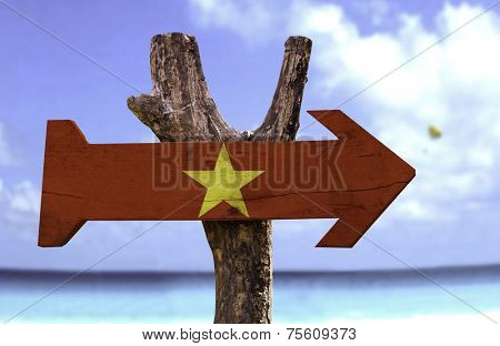 Vietnam wooden sign with a beach on background
