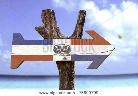 Dominican Republic wooden sign with a beach on background