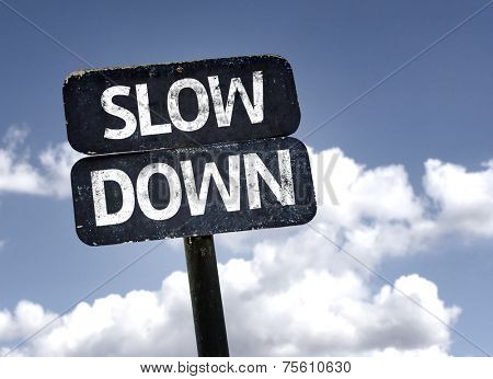 Slow Down sign with clouds and sky background