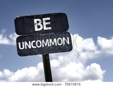 Be Uncommon sign with clouds and sky background