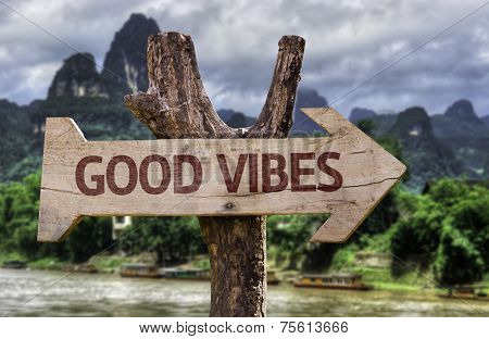 Good Vibes wooden sign with a forest background