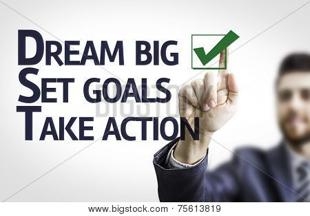 Business man pointing to transparent board with text: Dream Big / Seat Goals / Take Action