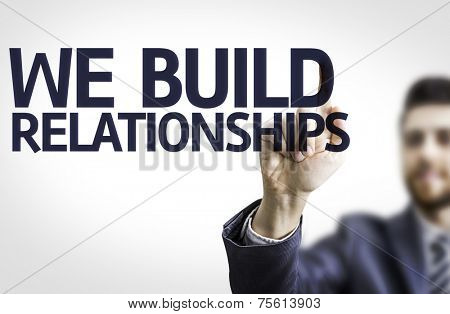 Business man pointing to transparent board with text: We Build Relationship