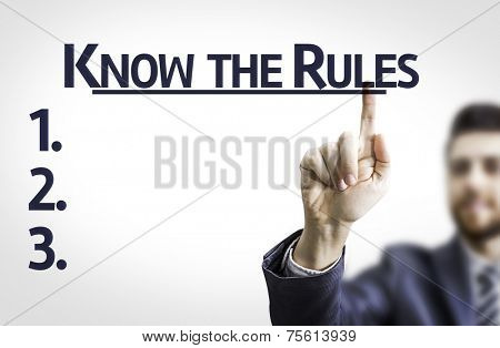 Business man pointing to transparent board with text: Know the Rules