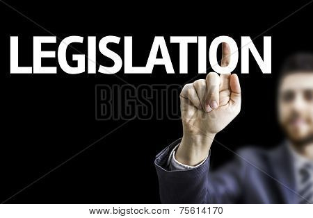 Business man pointing to black board with text: Legislation