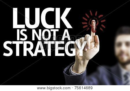 Business man pointing to black board with text: Luck is Not a Strategy