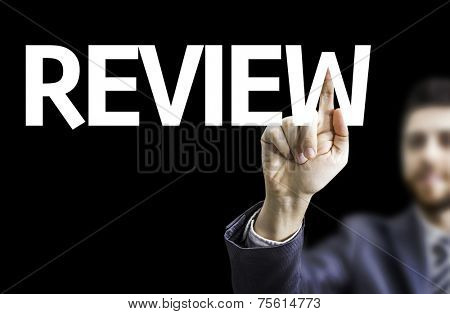 Business man pointing to black board with text: Review