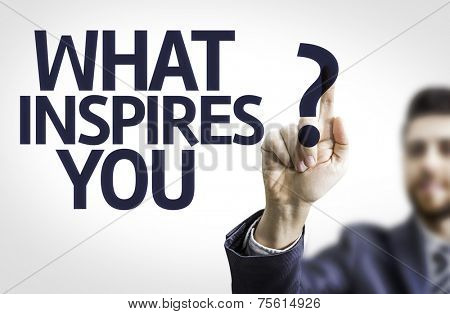 Business man pointing to transparent board with text: What Inspires You?