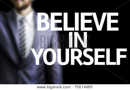 Believe in Yourself written on a board with a business man on background