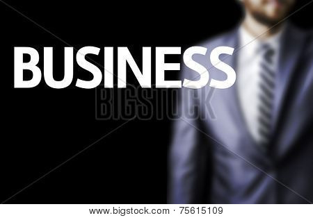 Business written on a board with a business man on background