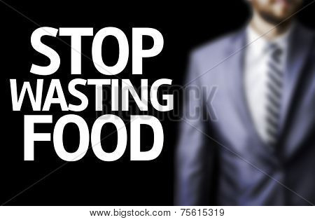 Stop Wasting Food written on a board with a business man on background