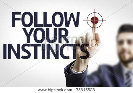 Business man pointing to transparent board with text: Follow your Instincts