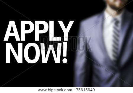 Apply Now! written on a board with a business man on background