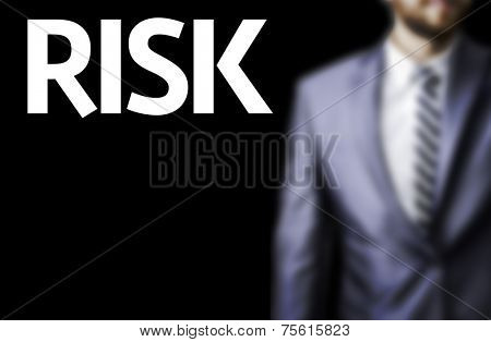 Risk written on a board with a business man on background
