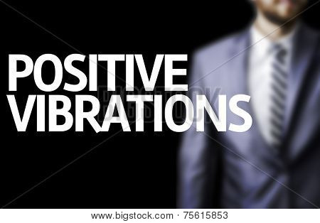 Positive Vibrations written on a board with a business man on background