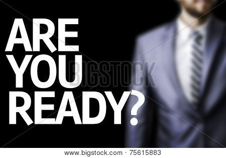 Are You Ready? written on a board with a business man on background