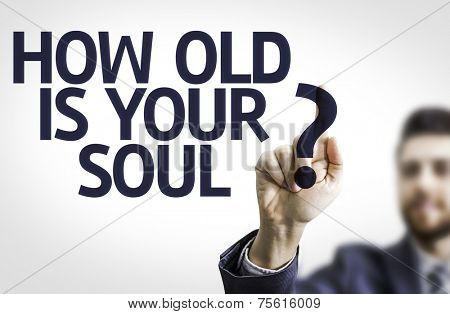 Business man pointing to transparent board with text: How Old Is Your Soul?