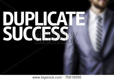 Duplicate Success written on a board with a business man on background