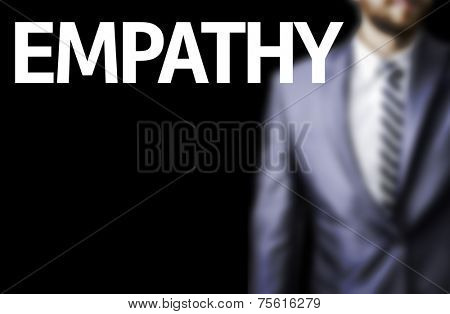 Empathy written on a board with a business man on background