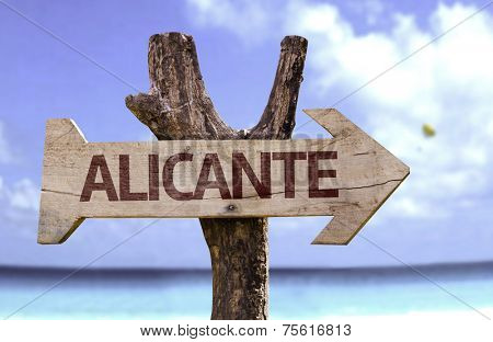 Alicante wooden sign with a beach on background