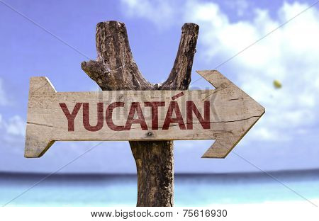 Yucatan wooden sign with a beach on background