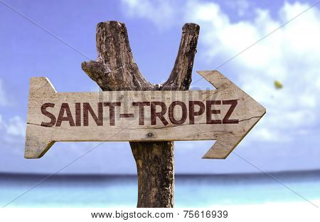 Saint-Tropez wooden sign with a beach on background