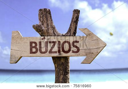 Buzios wooden sign with a beach on background