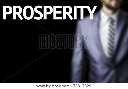 Prosperity written on a board with a business man on background