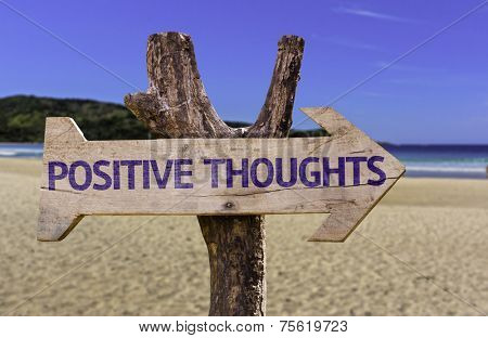 Positive Thoughts wooden sign with a beach on background