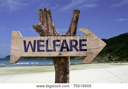 Welfare wooden sign with a beach on background