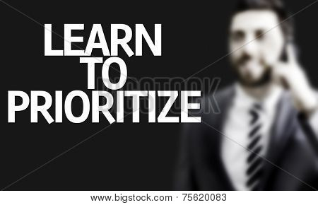 Business man with the text Learn to Prioritize in a concept image