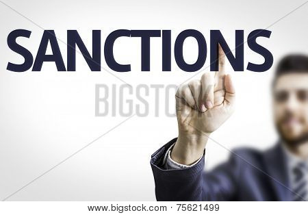 Business man pointing to transparent board with text: Sanctions