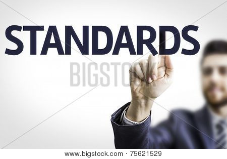 Business man pointing to transparent board with text: Standards