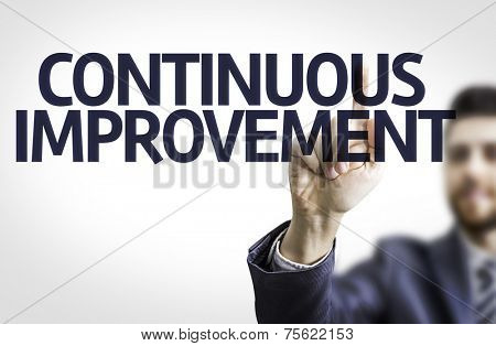 Business man pointing to transparent board with text: Continuos Improvement