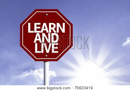 Learn And Live written on red road sign with a sky on background