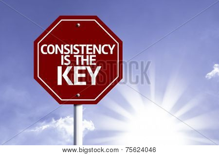 Consistency is The Key written on red road sign with a sky on background